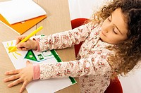 High angle view of a girl coloring on a sheet of paper