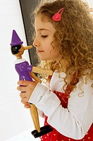 Side profile of a girl playing with a toy