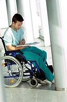 Side profile of a young man sitting in a wheelchair and reading a medical record
