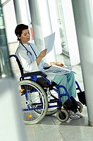 Female doctor sitting in a wheelchair and reading a medical record