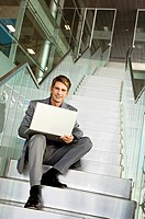 Portrait of a businessman sitting on a staircase and using a laptop (thumbnail)