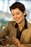 Close_up of a businesswoman operating a mobile phone and smiling