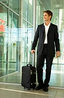Businessman standing with his luggage at an airport