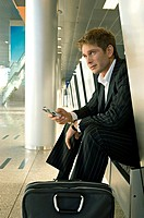 Businessman sitting at an airport lounge and operating a mobile phone