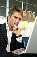 Businessman using a laptop in at an airport lounge