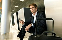 Businessman sitting at an airport lounge and holding a mobile phone