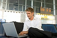Businessman using a laptop at an airport lounge
