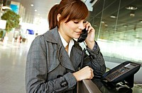 Close_up of a businesswoman talking on the telephone at an airport