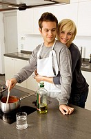 Young man cooking food and a young woman embracing him from behind in the kitchen