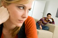 Close_up of a young woman thinking with a young man sitting on a couch in the background