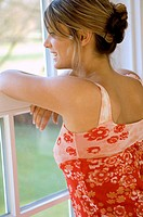 Close_up of a young woman looking through a window and smiling