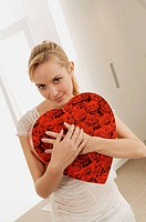 Young woman hugging a heart shape gift and smiling