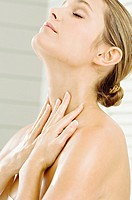 Close_up of a young woman applying moisturizer on her neck
