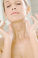 Close-up of a young woman rubbing ice cubes on her neck (thumbnail)