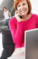 Close-up of a young woman using a laptop and talking on a mobile phone (thumbnail)