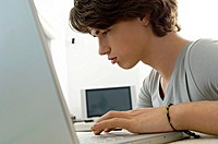 Close_up of a teenage boy using a laptop