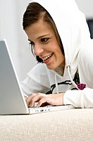Side profile of a young woman using a laptop and smiling