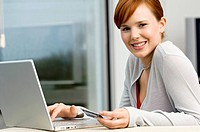 Portrait of a young woman holding a credit card and using a laptop