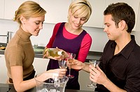 Young woman pouring wine for her friends (thumbnail)