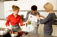Two young women helping a young man in wearing an apron in the kitchen (thumbnail)