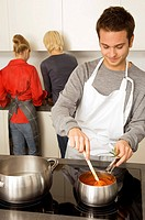 Young man cooking food and two young women standing behind him in the kitchen (thumbnail)