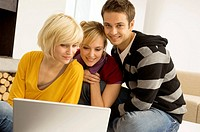 Two young women and a young man sitting in front of a laptop and smiling