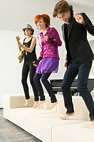 Two young women and a teenage boy dancing on a couch
