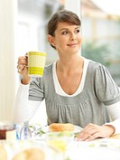 Young woman having breakfast and smiling