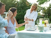 Woman serving water to her friends at garden party
