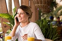 Smiling woman on cell phone at cafe