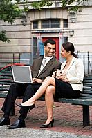 Smiling businesspeople outdoors with laptop