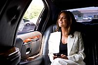 Businesswoman in backseat of car