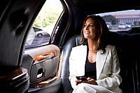 Businesswoman in backseat of car