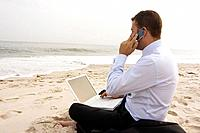 Businessman working on beach