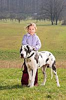 girl standing with Great Dane on meadow