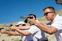 People aiming hand guns at firing range