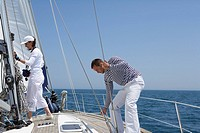 Two people working on a sailing boat
