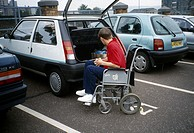 Young Man in Wheelchair Loading Boot of Car