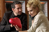 Man giving young woman a chocolate heart