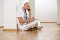 Mature man sitting on floor while phoning with a mobile phone