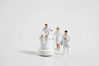 Figurines of doctors and stack of pills