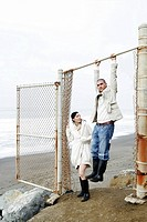 Man hanging from old fence with woman watching.
