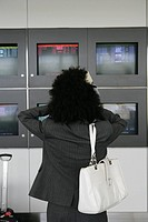 Stressed businesswoman in front of departure screens at airport.