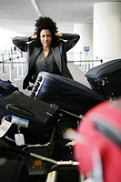 Stressed businesswoman looking at luggage at airport.