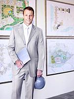 Businessman with hard hat in front of urban development plans