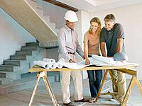 Construction foreman explaining blueprints to couple