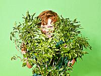 Young boy hiding behind green bush
