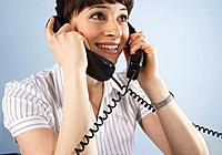 Businesswoman talking on two telephones