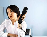 Businesswoman holding telephone away from her ear