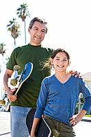 Portrait of grandfather and granddaughter with skateboards
